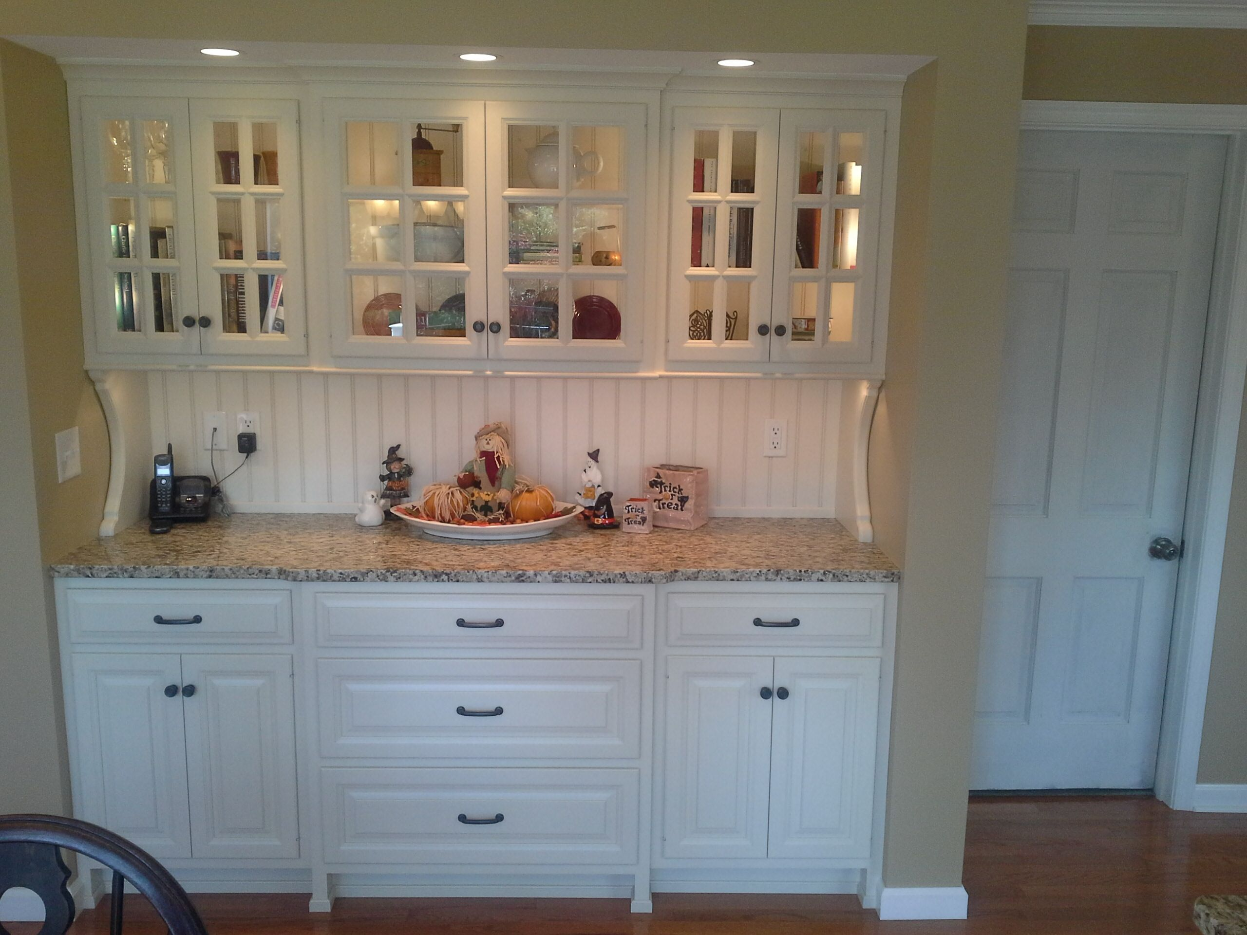 this custom kitchen design features a white painted hutch with
