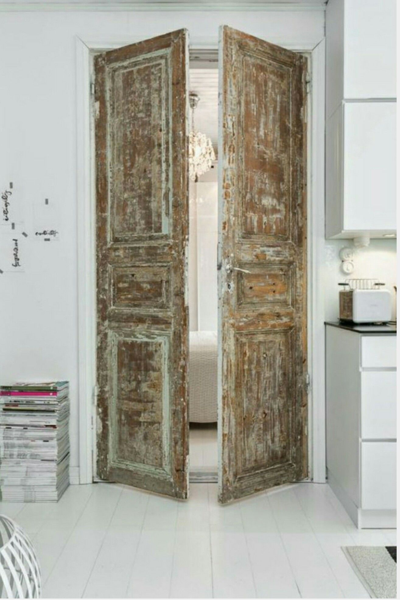 Antique Doors With Beautiful Patina Leading To Minimal White Kitchen
