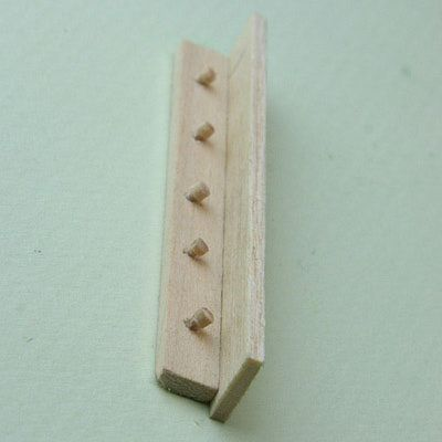 Dolls house shelf with pegs glued in place and upper shelf ledge glued to support.