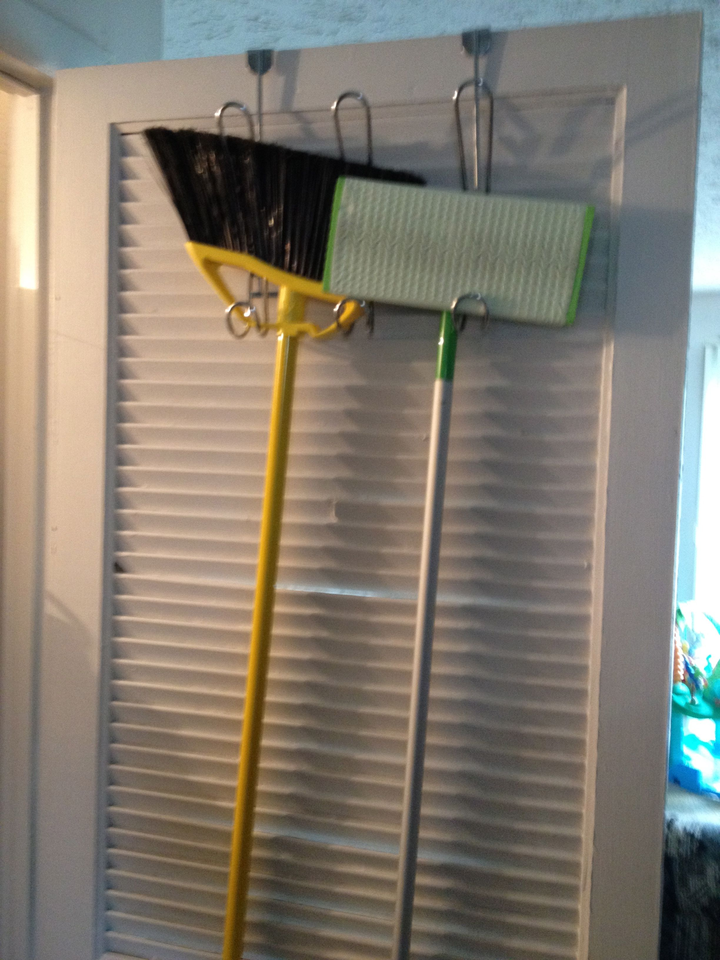 Use A Over The Door Hanger To Store Your Broom And Mop