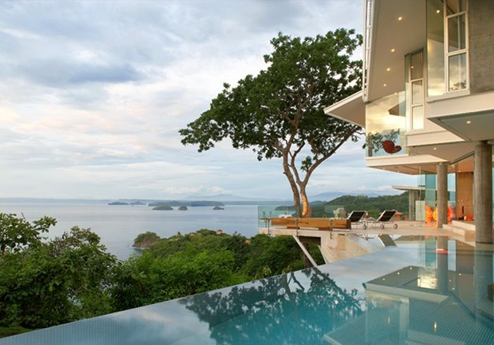 house in Costa Rica designed by Victor Cañas – architect and former diplomat. Situated in a long narrow field overlooking the sea and volcanoes in the distance. Made by concrete, steel and lots of glass