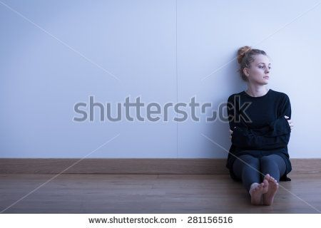 Lonely thoughtful girl sitting on the floor - stock photo