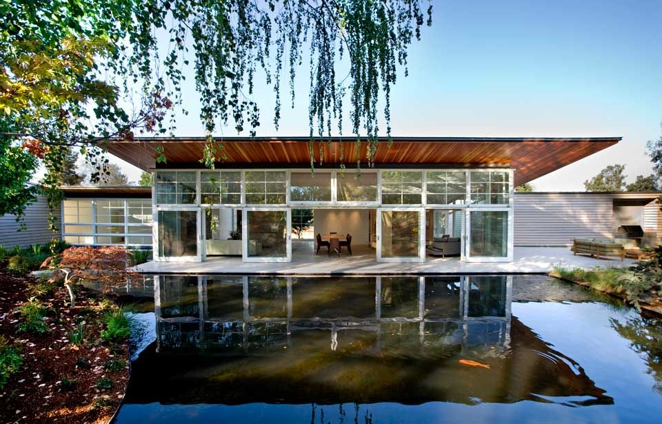 Sustainable home wraps around man made pond and lush for Home pond design