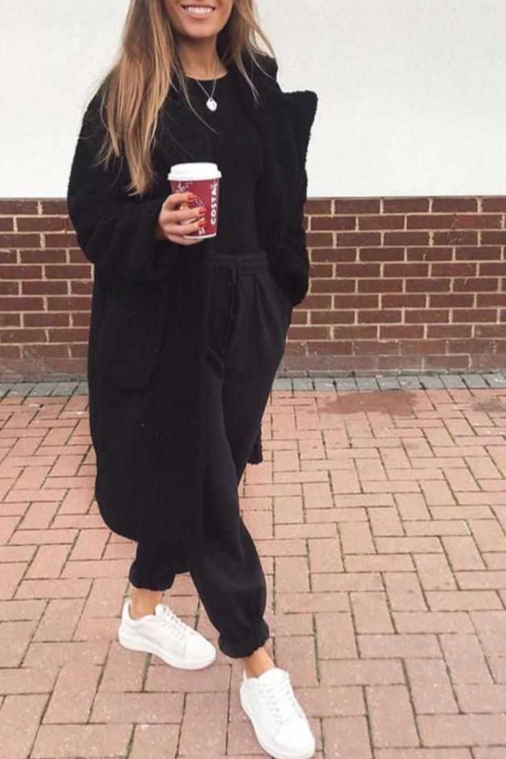 Modische Frau hält bequem, lässig mit einem schwarzen Jog, einem langen schwarzen Mantel ... - #Bequem #einem #Frau #hält #Jog #langen #lassig #Mantel #mit #modische #schwarzen #casualstylefall