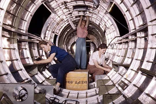"""Women workers install fixtures and assemblies to a tail fuselage section of a B-17 bomber at the Douglas Aircraft Company plant, Long Beach, Calif. Better known as the """"Flying Fortress,"""" the B-17F is"""