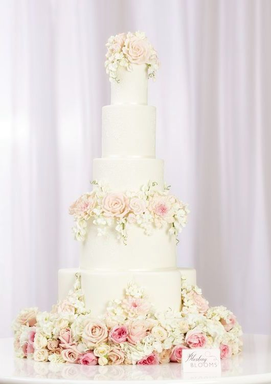 Glamorous five tier white wedding cake covered with blush colored flowers; Featured Cake: Peggy Porschen Cakes