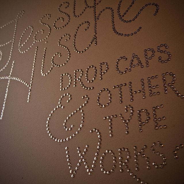 words with thumb tacks on wall or canvas