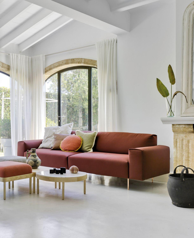 Terracottafarbenes Vierer Sofa Vor Weißen Wänden In Lichtdurchflutetem  Wohnzimmer