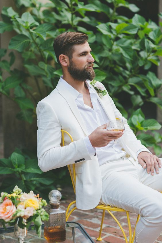 a white suit and shirt, a tropical flower boutonniere and a ...