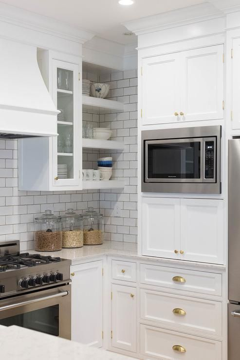 A Stainless Steel Microwave Is Mounted Between White Shaker