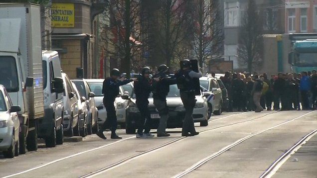 Shots have been fired and a police officer injured during an anti-terror raid in Brussels linked to the Paris massacre. Two men with Kalashnikov assault rifles opened fire on officers when they arrived at a house in the Belgian capital.