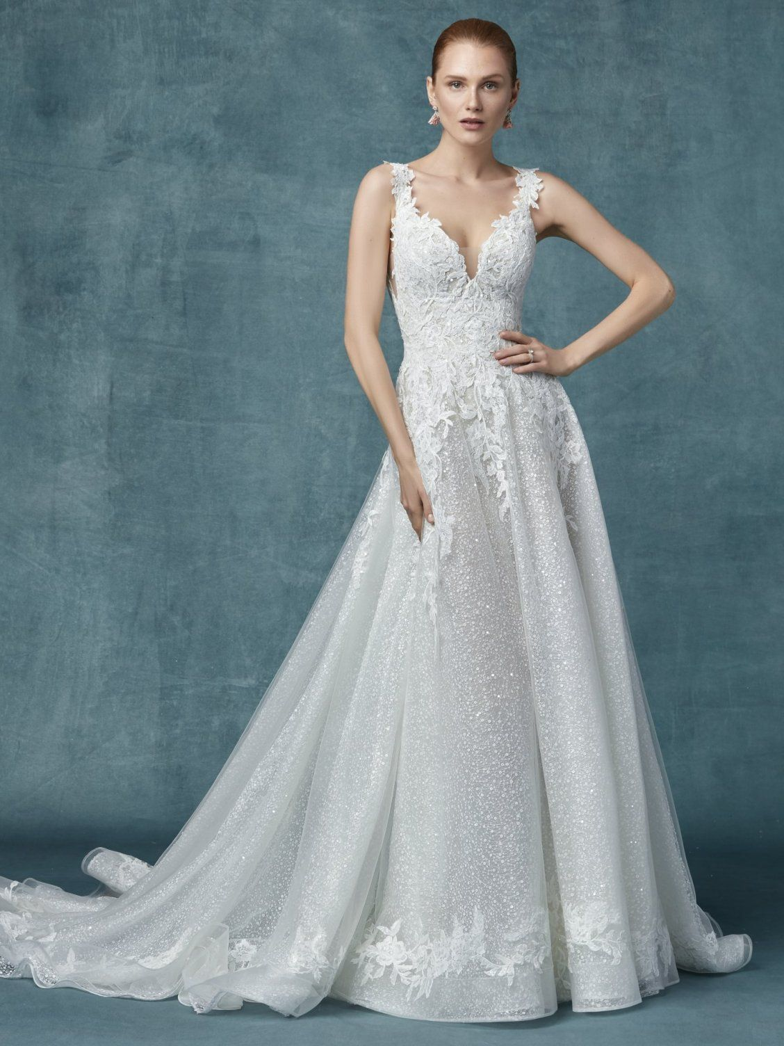 b067f4decf2 ... Romantic lace motifs drift over the bodice and hemline of this unique wedding  dress