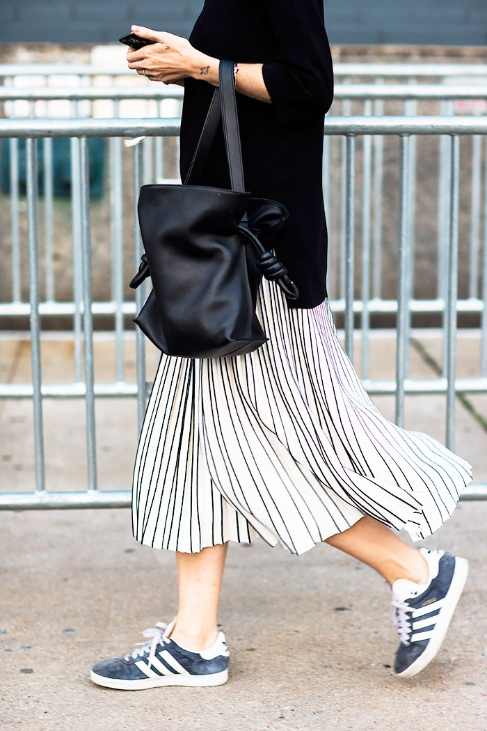 A black sweater is paired with a black and white pleated skirt, top-handle bag, and adidas sneakers