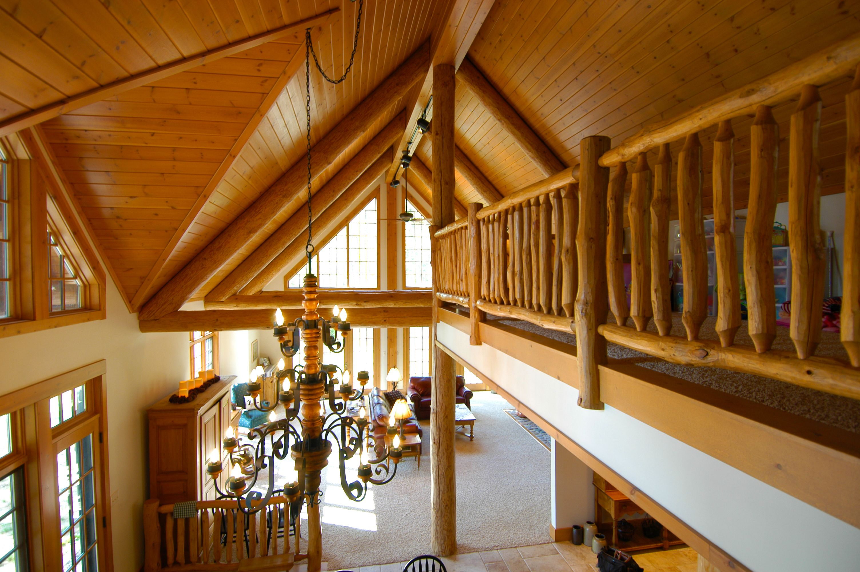 Log Railing Along The Loft With A Wood Ceiling And Log