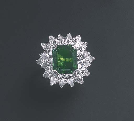 AN EMERALD AND DIAMOND RING, BY HARRY WINSTON  Set with a cut-cornered rectangular-cut emerald, weighing approximately 5.58 carats, within a circular and pear-shaped diamond two-tiered surround, mounted in platinum, in a Harry Winston black suede case Signed Winston for Harry Winston