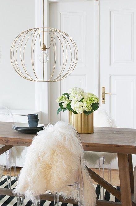 Ein Schwerer Holztisch, Hussenstühle Und Felle Machen Dieses Esszimmer  Gemütlich. Die Avantgardistische Leuchte Im Wire Design Sorgt Für Den  Luxuriösen Und ...