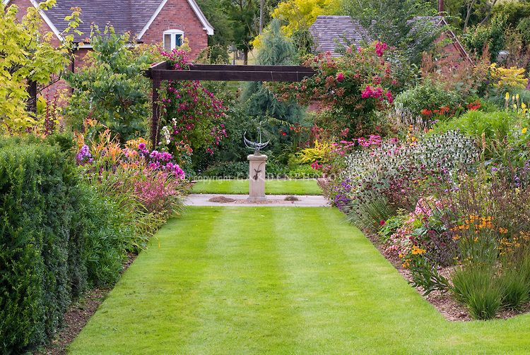 View Of Garden Beds Ornamental Armillary Sundial Brick House Lawn Grass Climbing Roses Lush Flowers Symmetrical Formal Design Style
