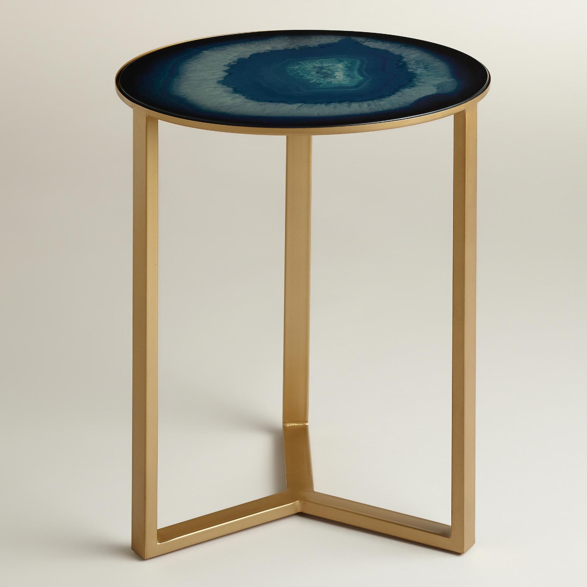 Our sleek table features a gold-finished three-legged metal frame ...