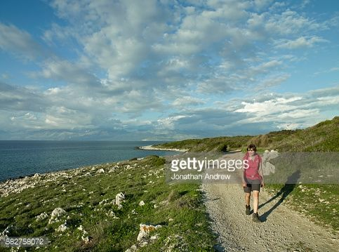 Female hiker walking on a rural road at Cape Agios Aikaterini,... #agiosgeorgiosargyradon: Female hiker walking on… #agiosgeorgiosargyradon