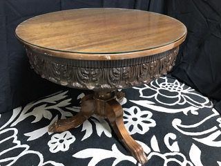 BEAUTIFUL OCCASIONAL PEDESTAL TABLE WITH HEAVILY CARVED SKIRT AND PAW FEET. IT HAS A PROTECTIVE GLASS TOP AND IS IN NICE, CLEAN CONDITION BUT THERE ARE A FEW NICKS PRESENT. 30H X 33W