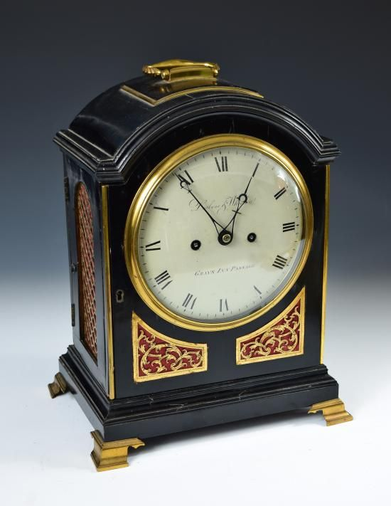 Sale F251115 Lot 677  A Regency ebonised bracket clock by Desbois & Wheeler, London, the single pad top with brass handle, 17cm (6.5in) circular enamel dial marked 'Desbois & Wheeler, Grays Inn Passage', twin fusee movement with signed backplate, the door with engraved brass lower spandrels, brass scale side frets, upon ogee brass feet h:36 w:28.50 cm  - Cheffins