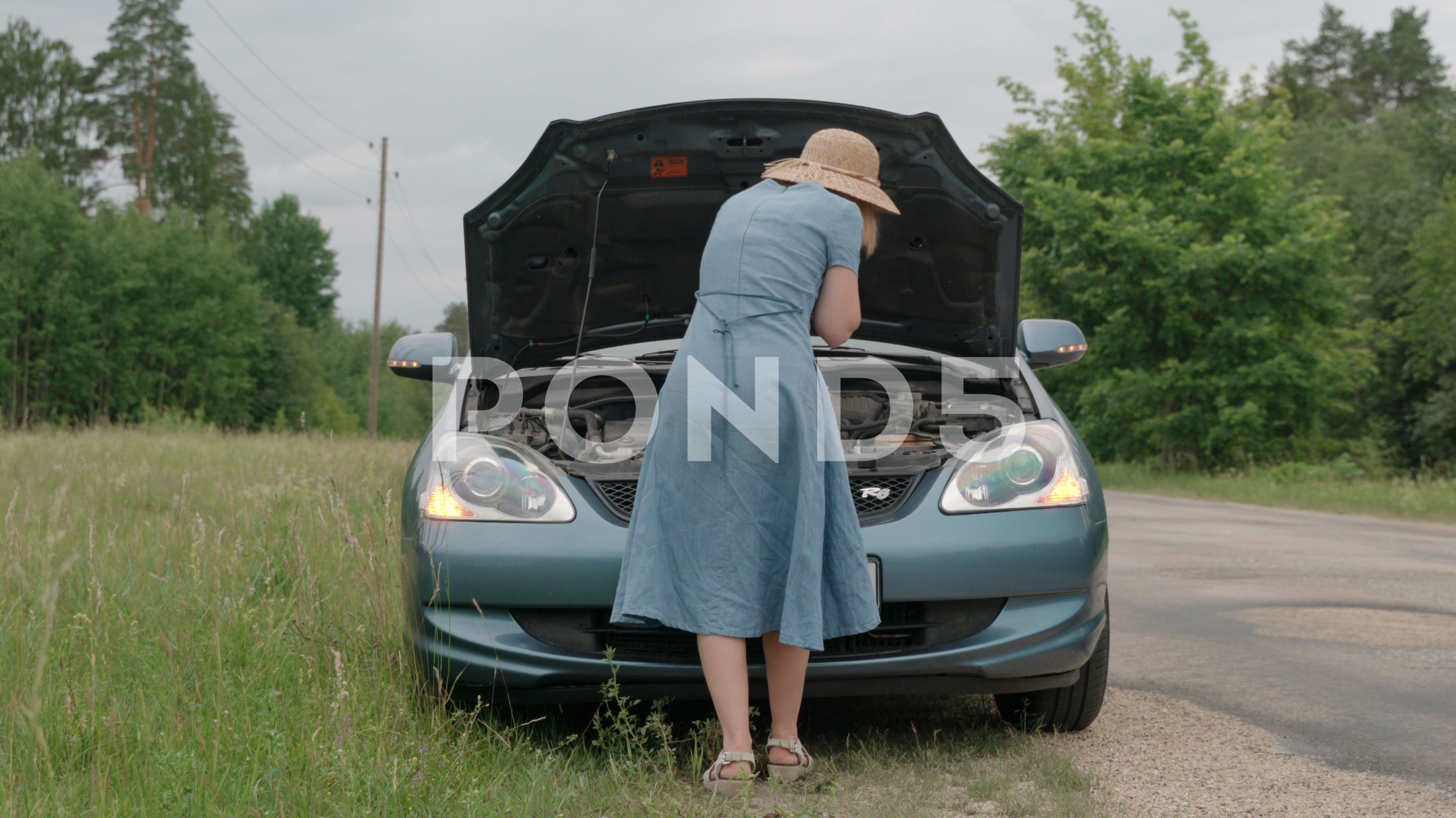 Confused woman looking under the hood of her broken