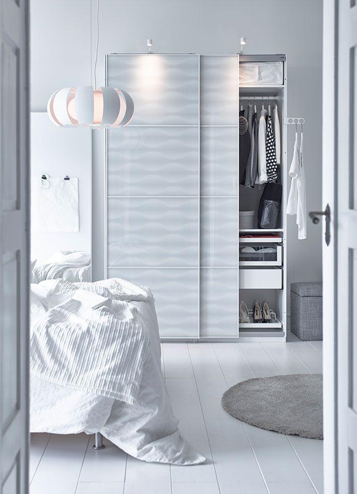 Un dormitorio con un armario blanco con puertas de vidrio for Armario blanco puertas correderas ikea