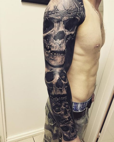 372624aa5 Guys sleeve with four skulls the top one wears a crown of thorns ...