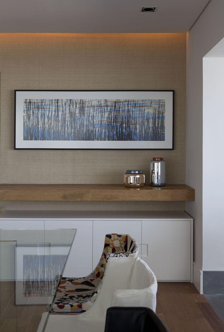 Sala de jantar com mesa em vidro incolor e cadeiras coloridas estofadas. Existe um aparador branco, com puxadores na própria porta tipo encaixe. Acima, uma prateleira de madeira na altura da mesa, visto que o aparador é muito baixo. A parede ganha destaque com um papel de parede tipo tecido de palha e um quadro de pintura.