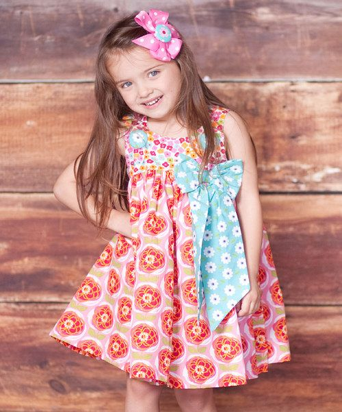 This darling dress' perfectly pretty silhouette features a playful print that's wonderfully lovable. A full skirt and a big contrasting bow add irresistible sweetness to its fun-loving form.