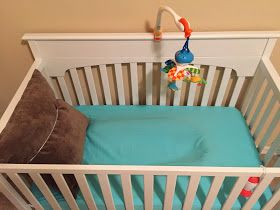Great ideas for transitioning to crib from Rock n Play- I like the idea to use a rolled up beach towel under the crib sheet!