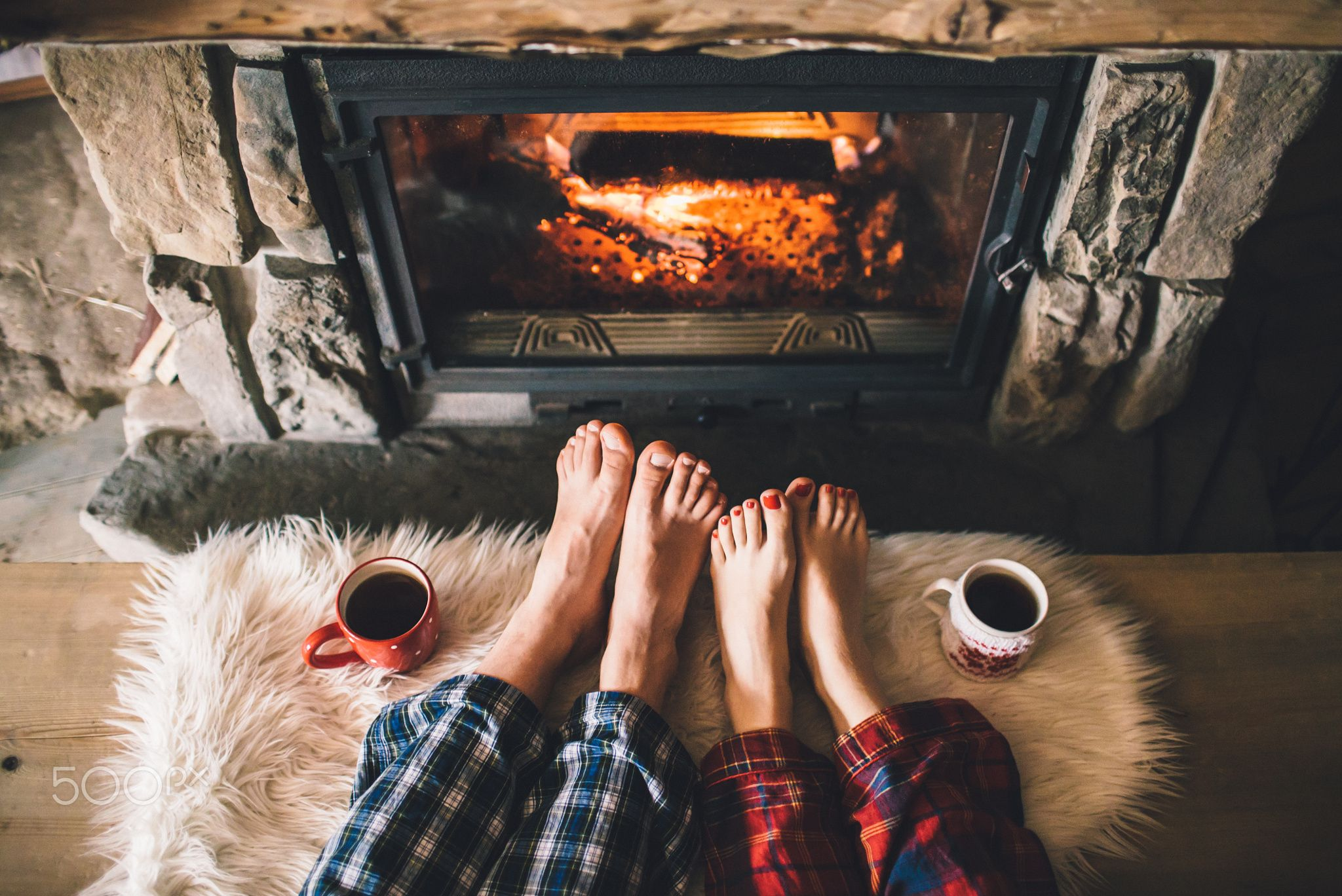 bare couple feet by the cozy fireplace man and woman relaxes by