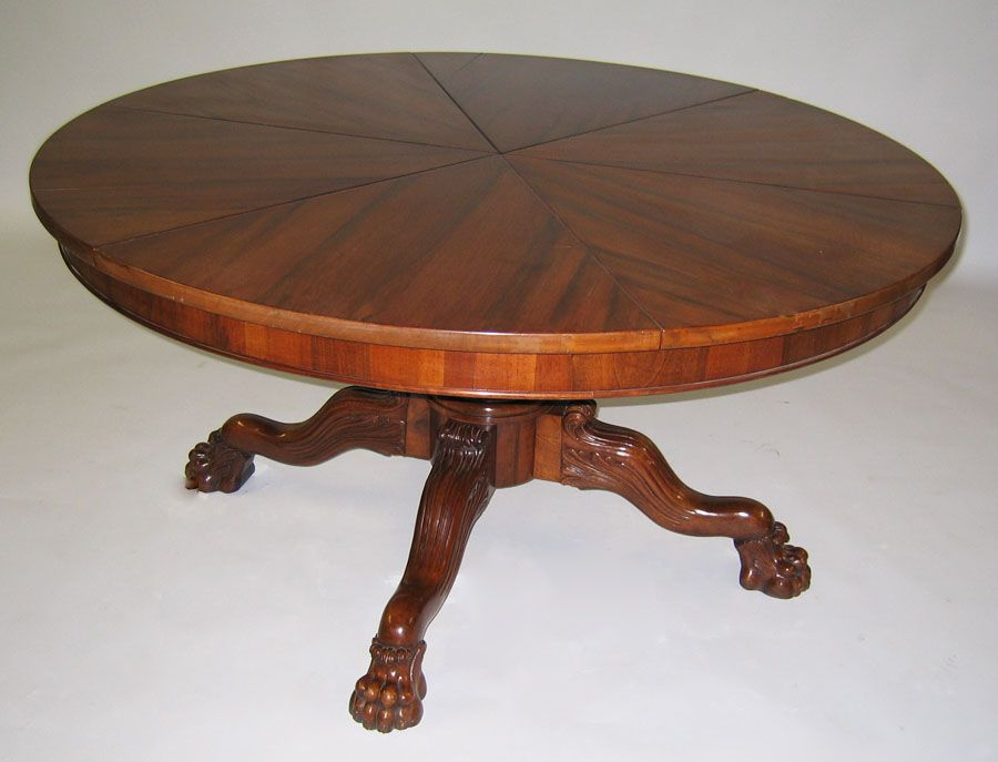 A Large Carved Walnut Expanding Circular Dining Table With A Segmented Top,  After Robert Jupe