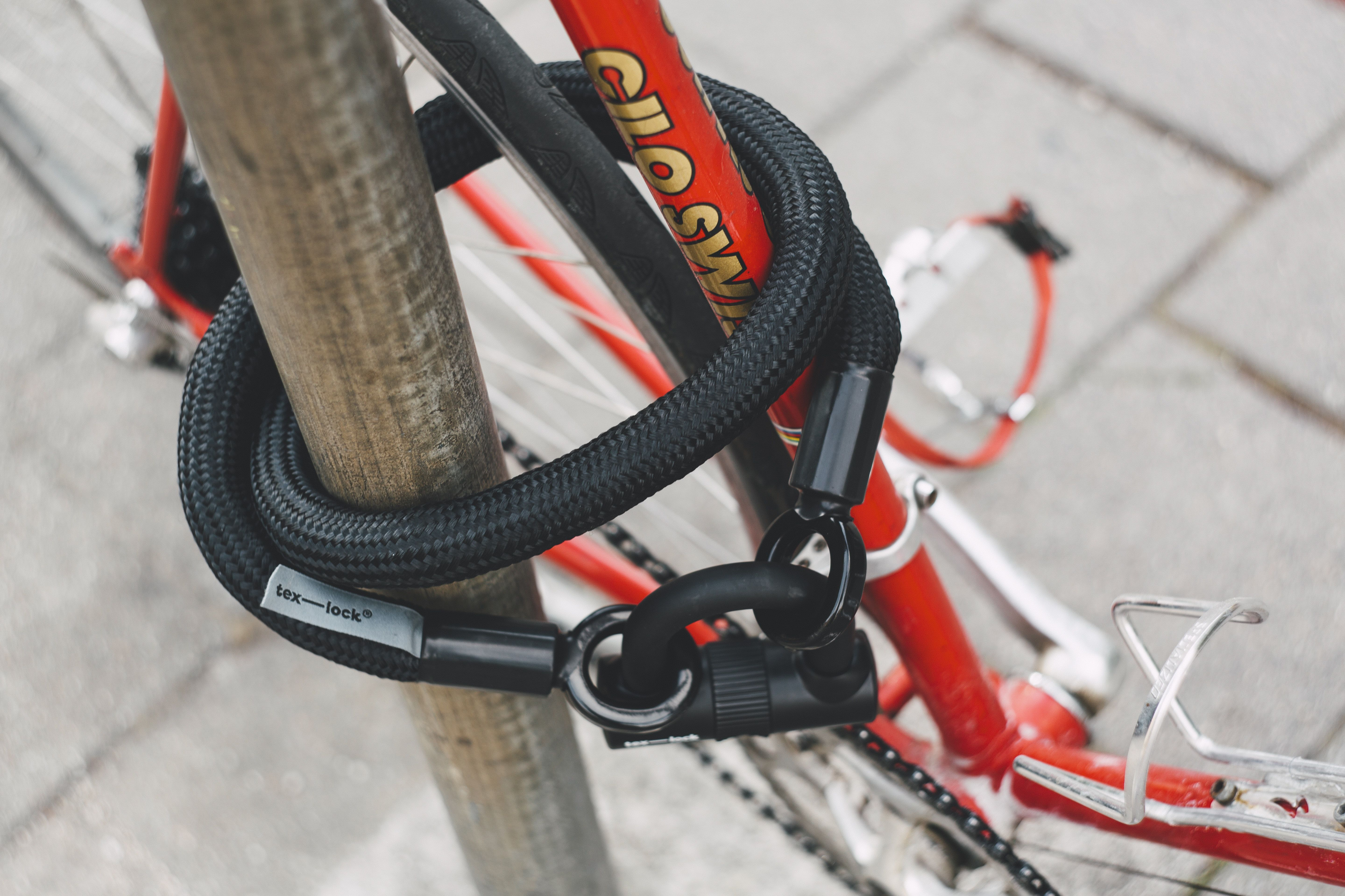 Red And White Bicycle Locked In Gray Pole White Bicycles