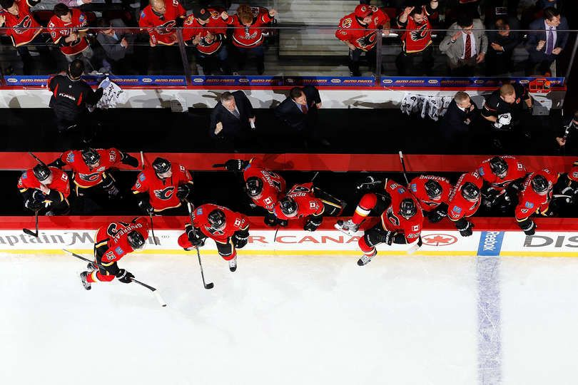 CALGARY, AB - APRIL 21: Teammates of the Calgary Flames jump over the bench to celebrate after a 3-1 win against the Vancouver Canucks at Scotiabank Saddledome for Game Four of the Western Quarterfinals during the 2015 NHL Stanley Cup Playoffs on April 21, 2015 in Calgary, Alberta, Canada. (Photo by Gerry Thomas/NHLI via Getty Images)