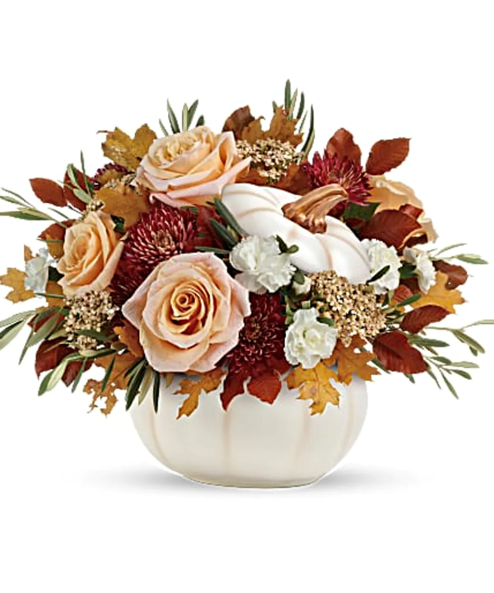 Elegant crème roses blend with the heartwarming hues of