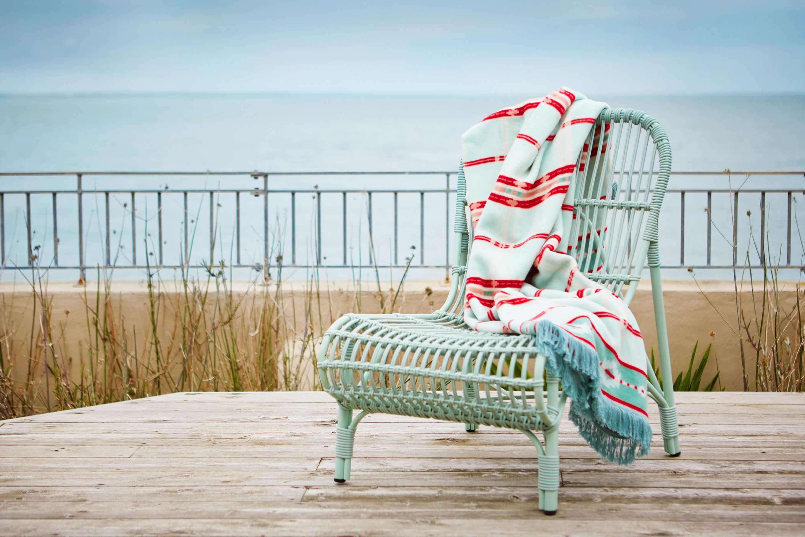 Woven chair and patterned blanket with fringe detail by