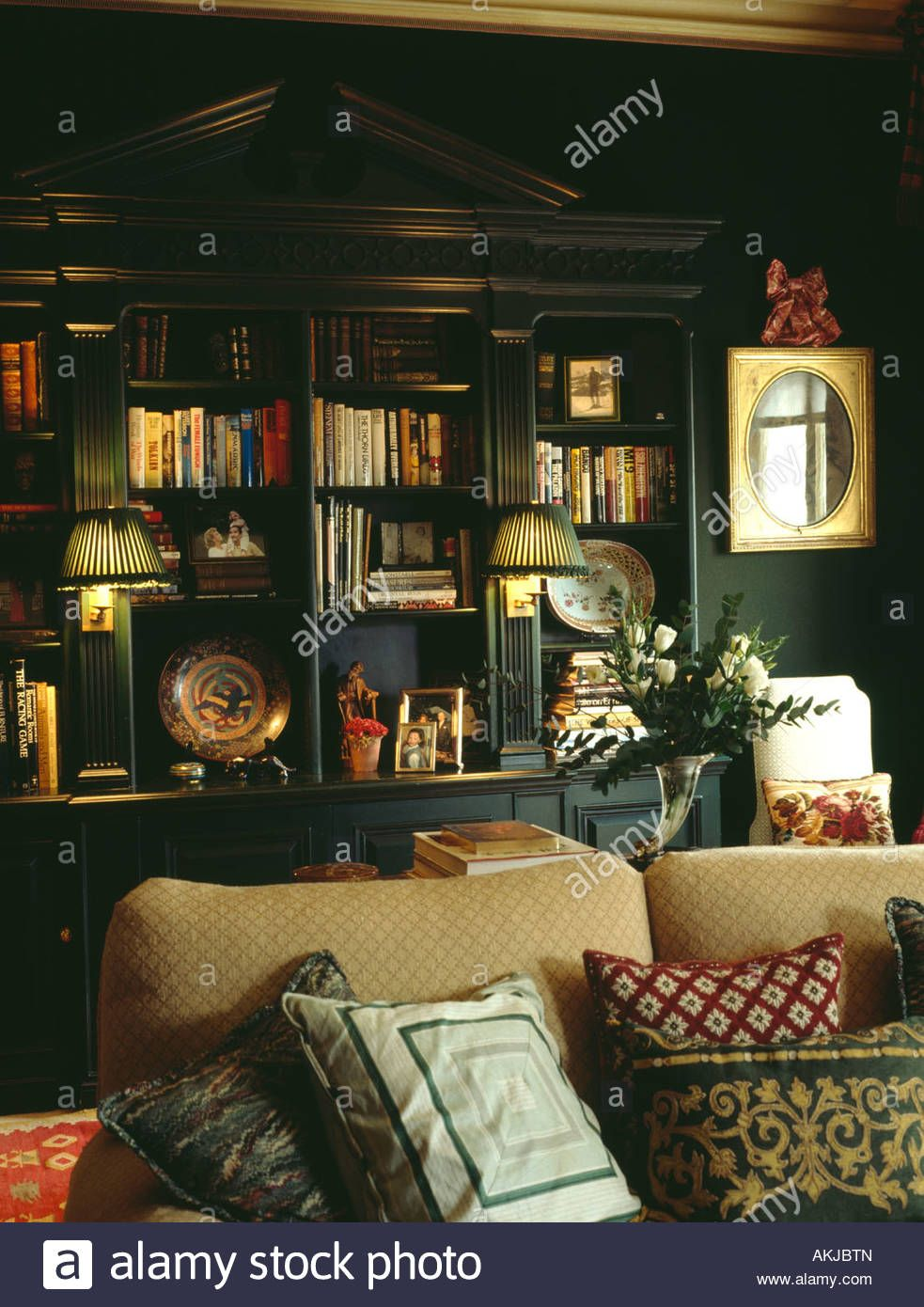Lighted lamps on fitted bookshelves in dark green living