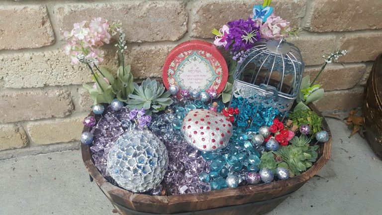Glass beads, bird cage sprayed silver from the $2 shop, clay toadstools sprayed silver and dipped with glitter. Fake blooms and small cacti added and a silver glitter ball from a thrift shop included.