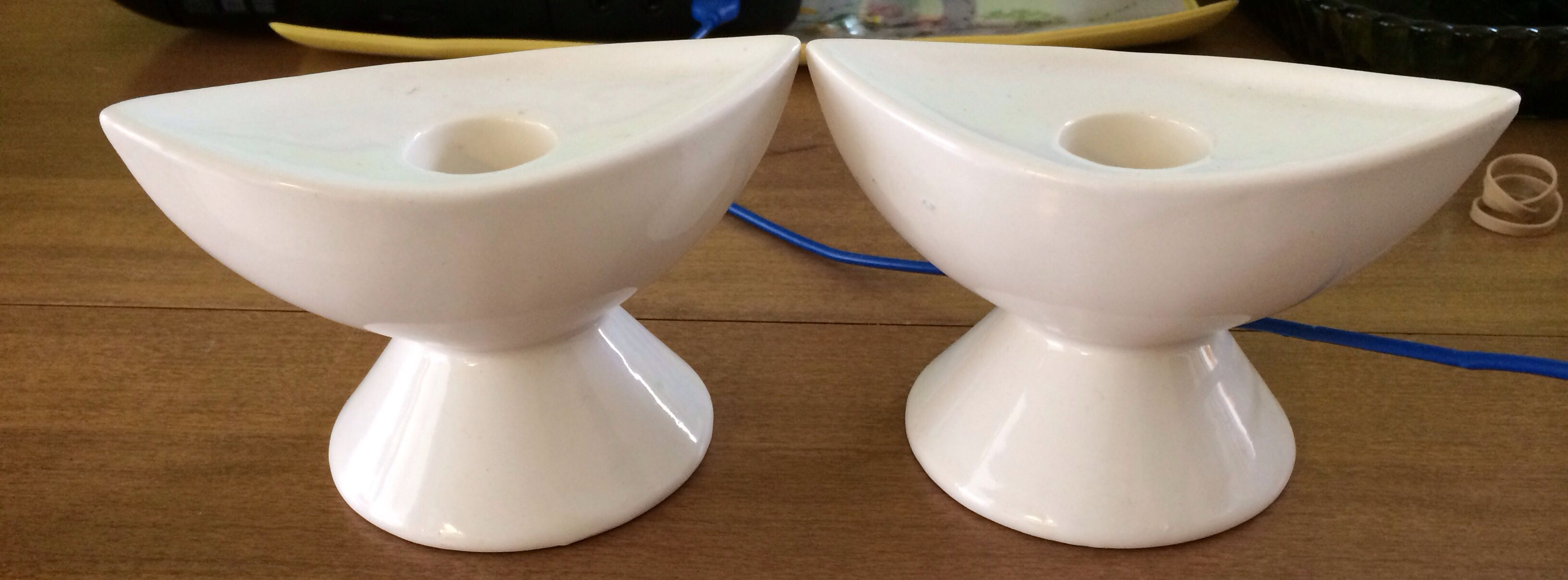 "These mid century modern candle holders are white in a simple canoe shape. They are 4 1/2"" x 2 1/4"" and 3"" tall. They are in great shape, with no chips or cracks, and only some scuffing on the bases. They are faintly marked ""USA 42.""  We estimate the cost of shipping from coast to coast, and all shipping includes delivery confirmation. We will refund any difference greater than $1 between the shipping charges paid and the actual cost of shipping."