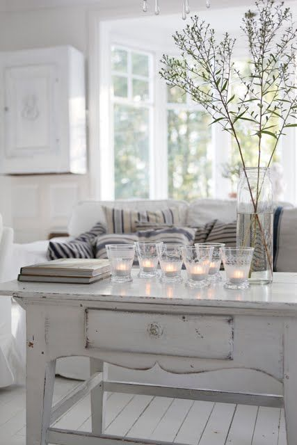 amazing whites, nice use of colour in the cushions, flowers & candles..... looks like a cosy room for me <3