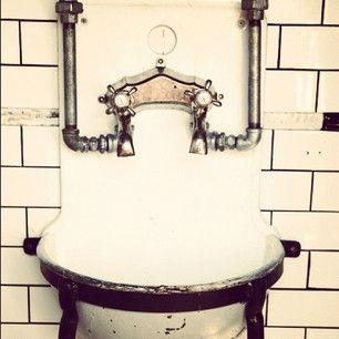 Old fashioned sink and plumbing and with tile splash-back ...