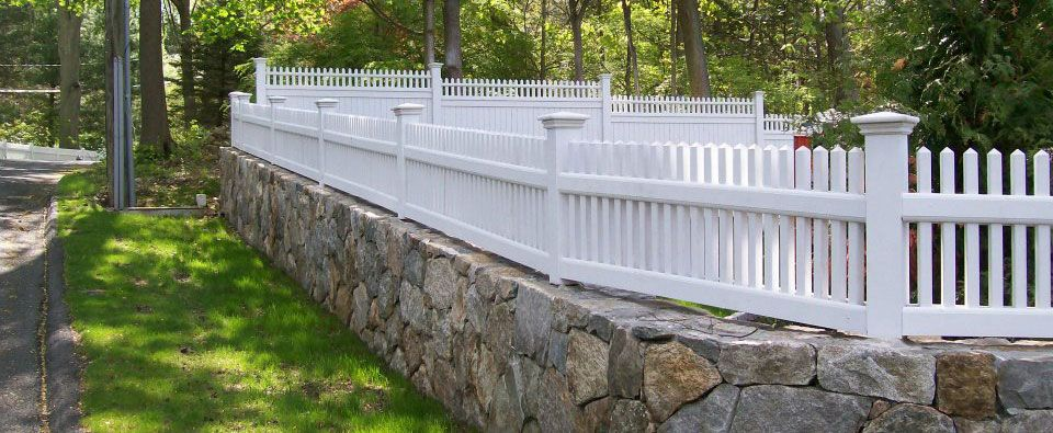Picket fence on stone wall installed by A Anastasio Fence Company