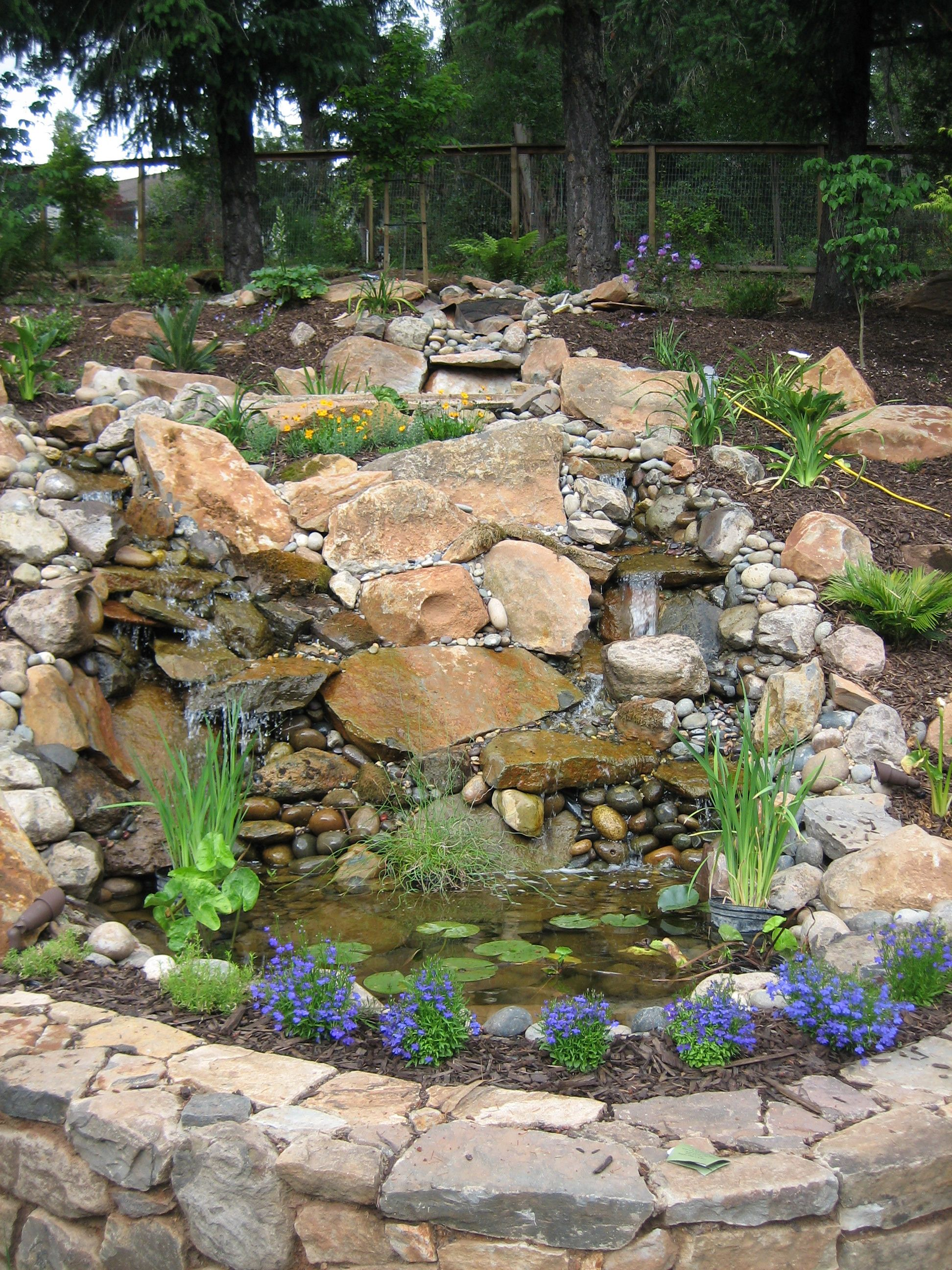 Backyard waterfall made from river rock and slate very natural