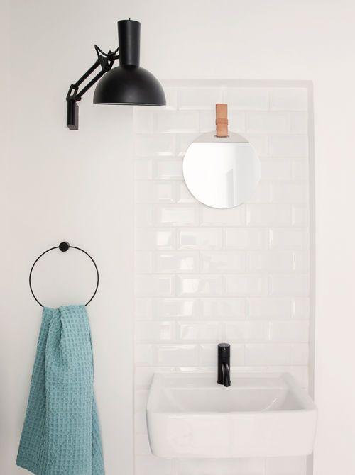 Handdoekring en zwarte wandlamp in badkamer