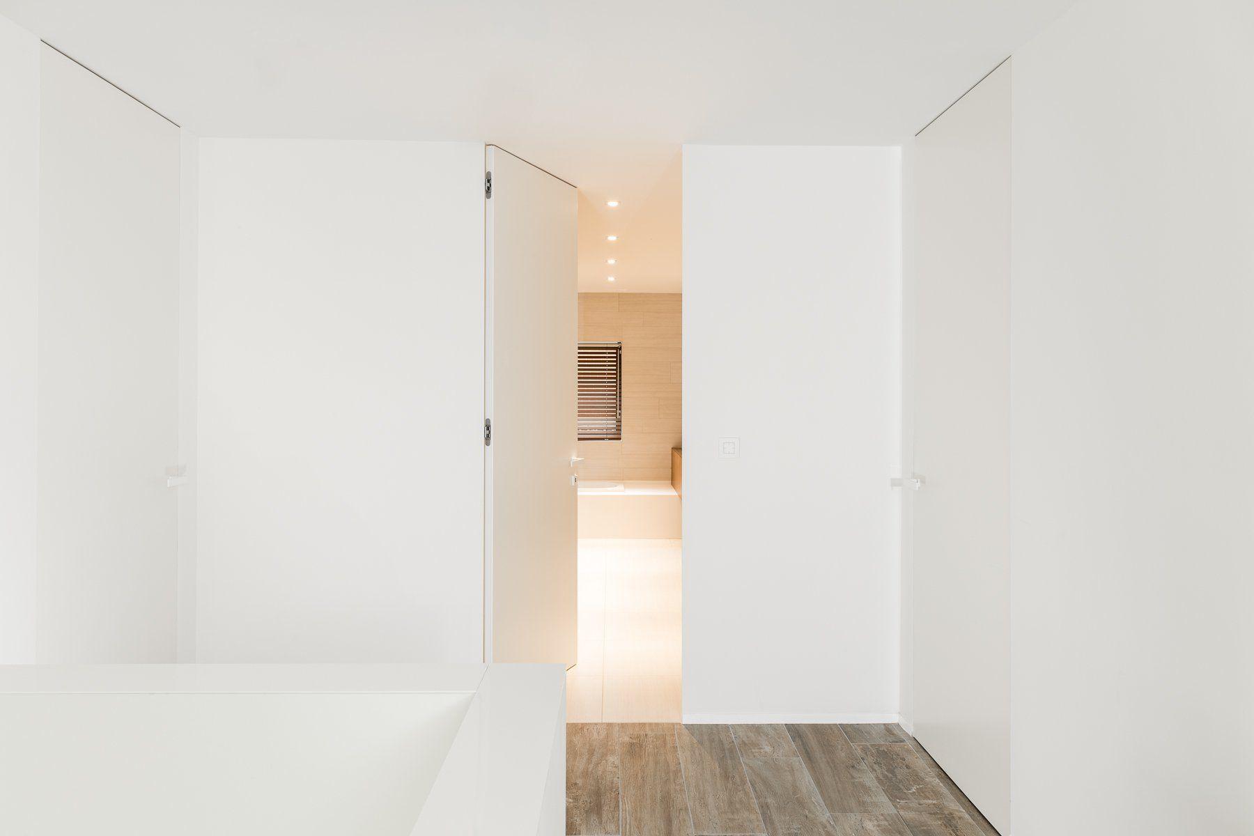 Een strakke moderne deur in dezelfde kleur als de muren wonen