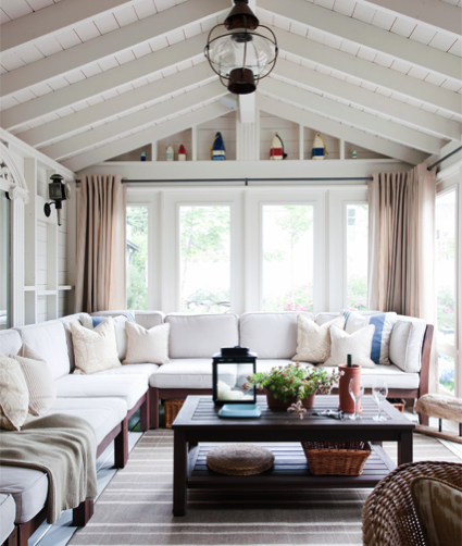 I like how cozy this sunroom feels- add a fireplace, flip the furniture around, and change the ceiling.
