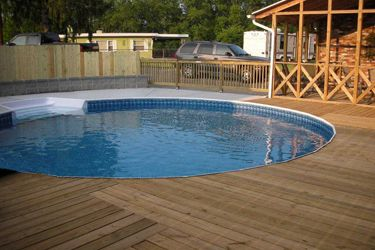 freedom above ground pool installed partially inground with combination wood and concrete deck and stairs