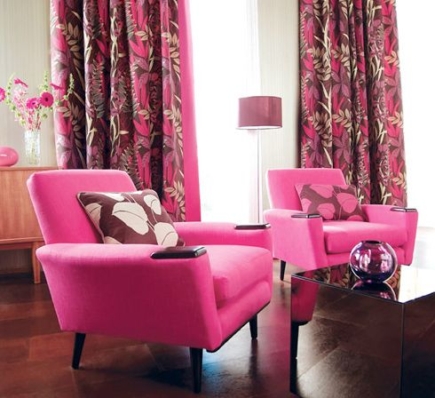 Hot pink chairs, floral design drapes and a bronze coffee table add ...