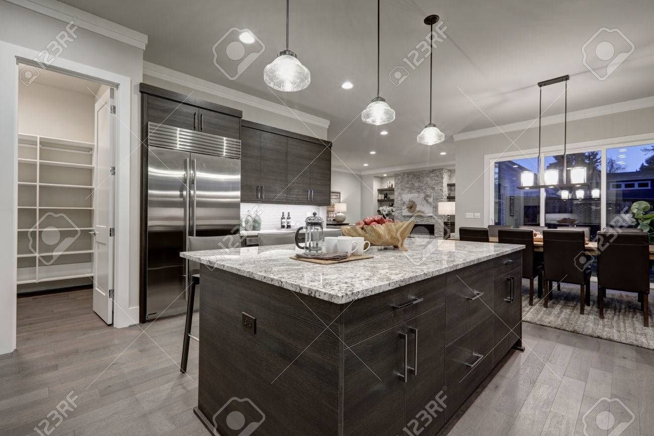 Modern open plan gray kitchen features dark gray cabinets paired in